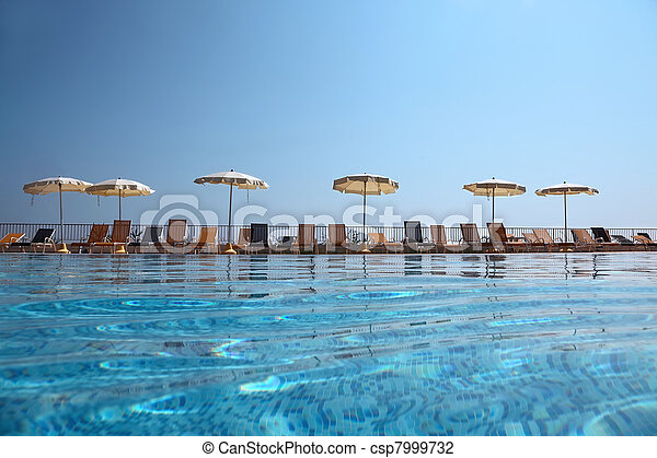 Captivating On Edge Of Pool Near Fence Deck Chairs Stand With Opened Beach Umbrellas,  Underwater Package Shot Stock Photo