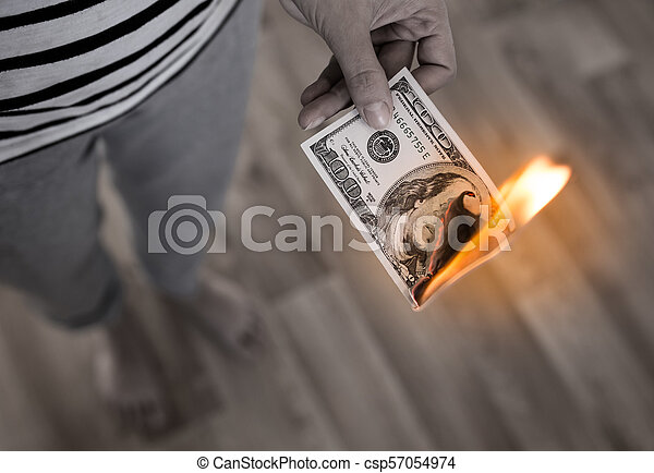 one hundred dollars burn in flames in hand - csp57054974