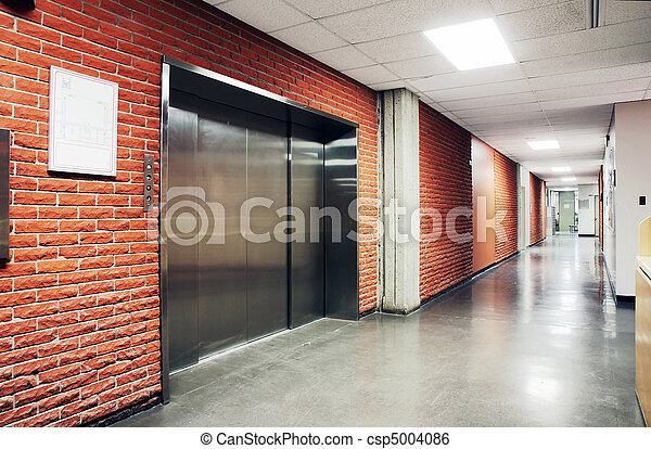One freight stainless steel door elevator surrounded by brcik wall of a deserted hallway. Could be office school retirement home and hospital. & One large steel door elevator. One freight stainless steel door ...