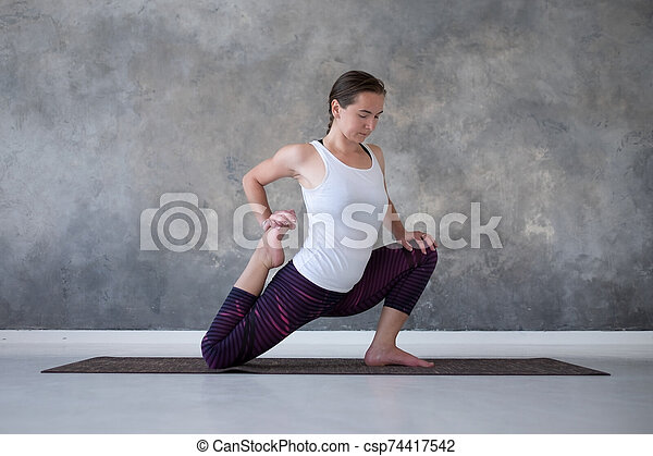 young happy woman practicing yoga sitting in one legged