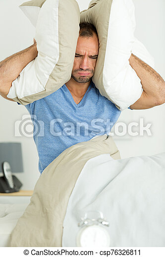 one man trying to sleep covering ears - csp76326811