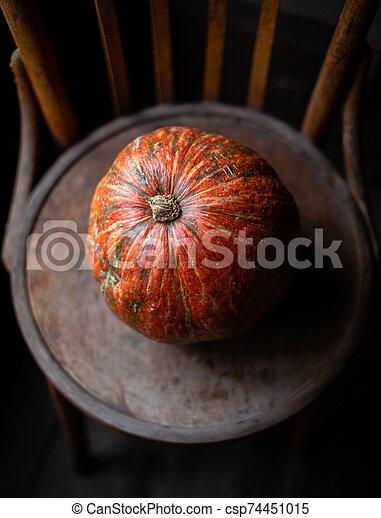 one orange pumpkin stands on old brown chair - csp74451015