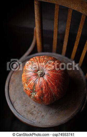 one orange pumpkin stands on old brown chair - csp74553741