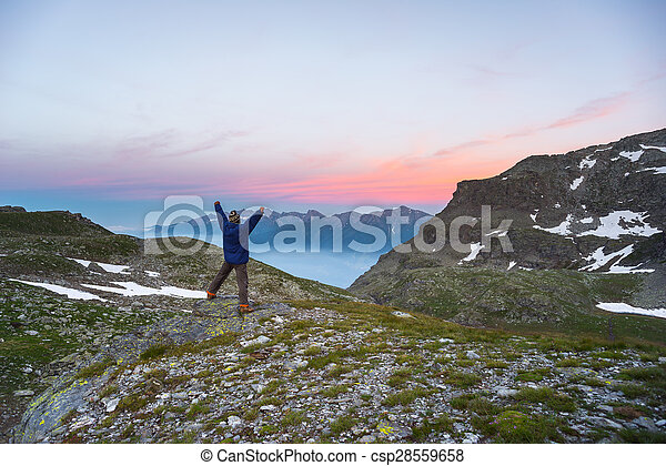 One person watching sunrise high up in the Alps - csp28559658
