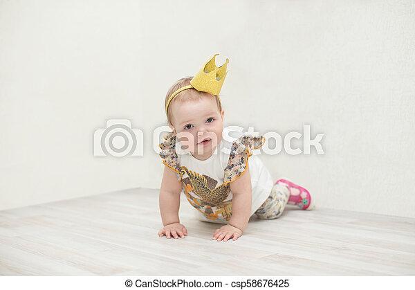Una niña de un año con una corona. La princesa se arrastra al suelo - csp58676425
