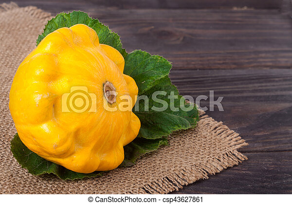 one yellow squash on a wooden background with napkin of burlap - csp43627861