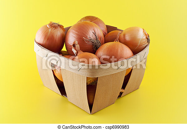 Onions in a box on yellow background. - csp6990983