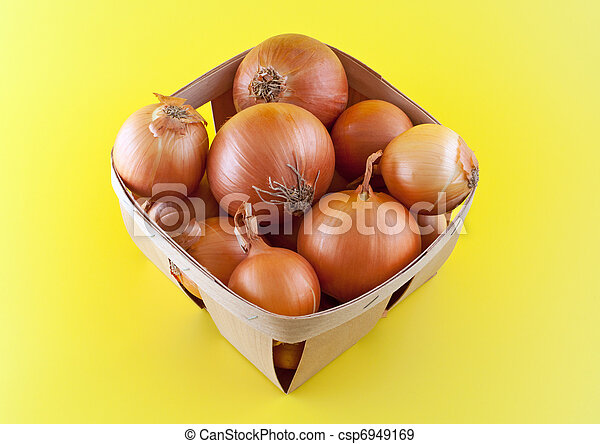 Onions in box on yellow background. - csp6949169