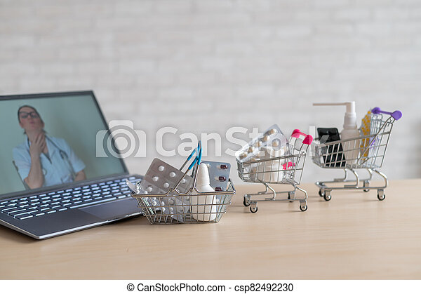Online medicine and pharmacy concept. A female doctor conducts an online consultation and recommends medications. Mini trolley with tablets at the laptop. - csp82492230