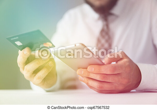 Online payments through the phone. Payment of goods online. Smartphone and Internet Commerce. Young businessman with a bank credit card in his hands. Online trading on the currency exchange. - csp67567532