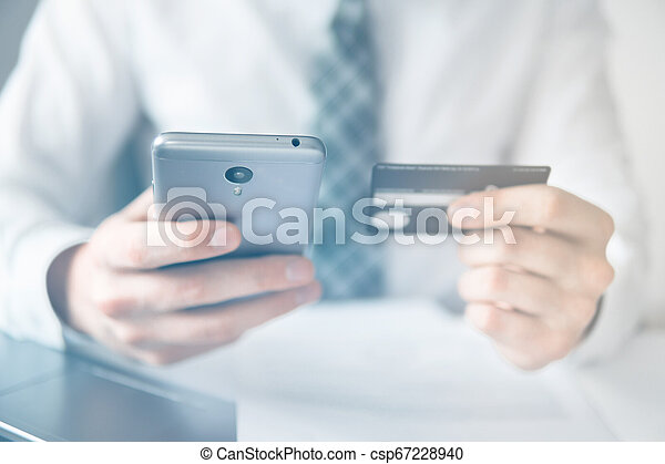 Online trading on the currency exchange. Smartphone and Internet Commerce. Online payments through the phone. Payment of goods online. Young businessman with a bank credit card in his hands. - csp67228940