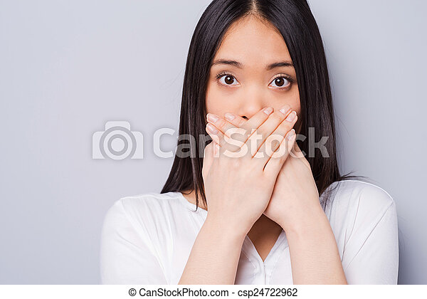 Oops! Surprised young Asian woman covering mouth with hands and staring at camera while standing against grey background - csp24722962