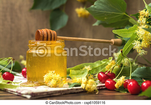 Open glass jar of liquid honey and honey dipper, bunch of linden flowers - csp61059116
