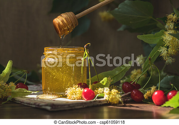 Open glass jar of liquid honey and honey dipper, bunch of linden flowers - csp61059118