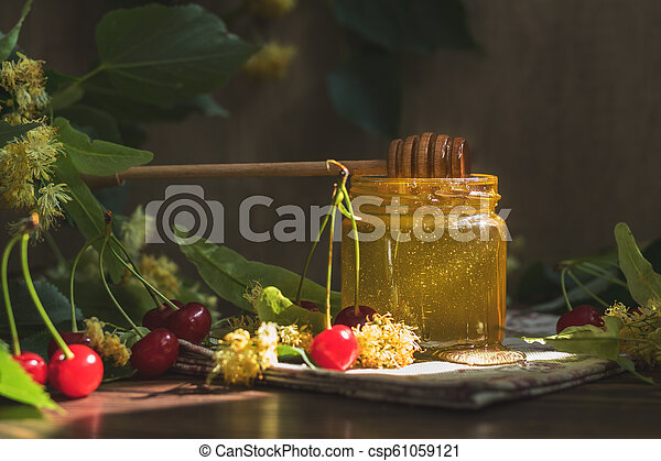 Open glass jar of liquid honey and honey dipper, bunch of linden flowers - csp61059121