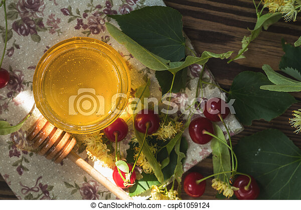 Open glass jar of liquid honey and honey dipper, bunch of linden flowers - csp61059124