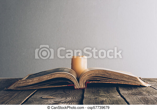 open holy bible with candle on wooden table - csp57739679