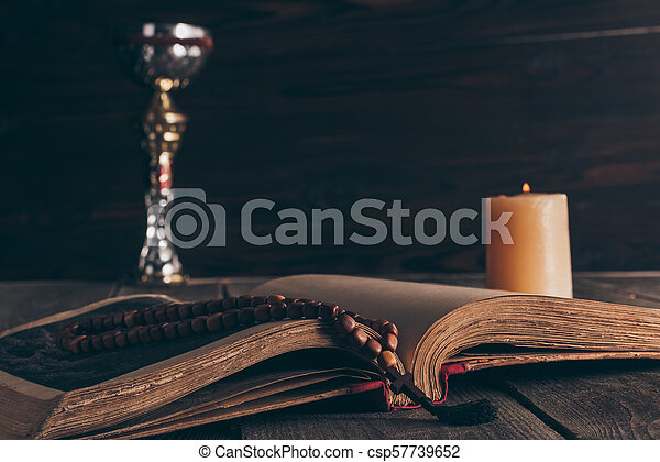 open holy bible with rosary, chalice and candle on wooden table, Holy Communion - csp57739652