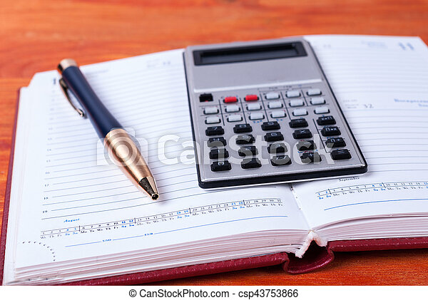 Open notebook with a calculator and a pen lying on it - csp43753866