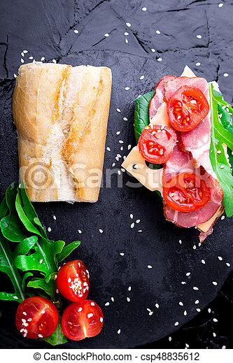 Open sandwich with jamon, arugula, tomatoes, cheese on stone slate black background. Top view - csp48835612