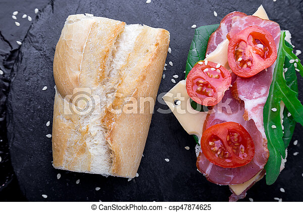 Open sandwich with jamon, arugula, tomatoes, cheese on stone slate black background. Top view - csp47874625