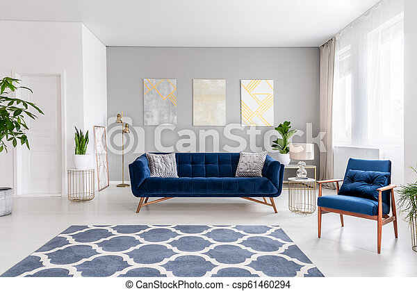 Open Space Living Room Interior With A Navy Blue Sofa And An Armchair Rug On The Floor And Graphic Decorations On The Wall