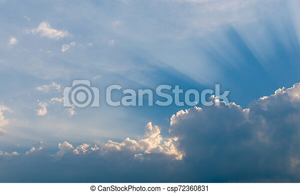 Optimistic sunset rays behind the clouds. Glow in the sky. Symbol of light. Beautiful scene of nature. - csp72360831