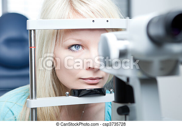optometry concept - pretty young woman having her eyes examined by an eye doctor on a slit lamp - csp3735728