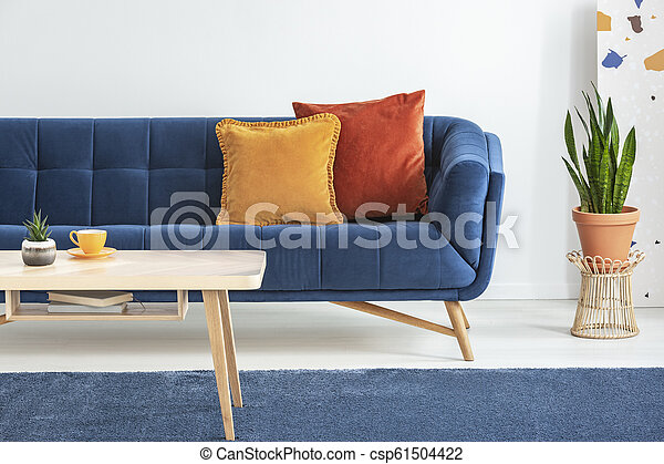 Orange and red cushions on a fancy, navy blue sofa and a basic, wooden  coffee table on a blue rug in a white living room interior. Real photo.