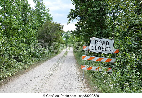 orange and white road closed sign with path or trail - csp83223820