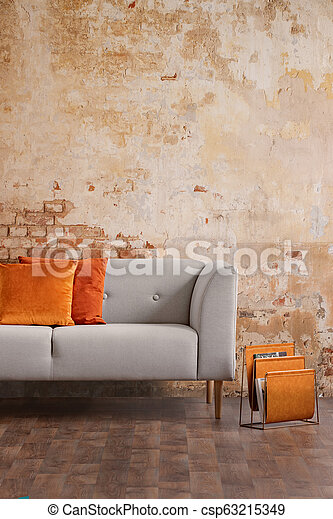 Orange Cushions On Grey Sofa Against Red Brick Wall In Modern Living Room Interior Real Photo