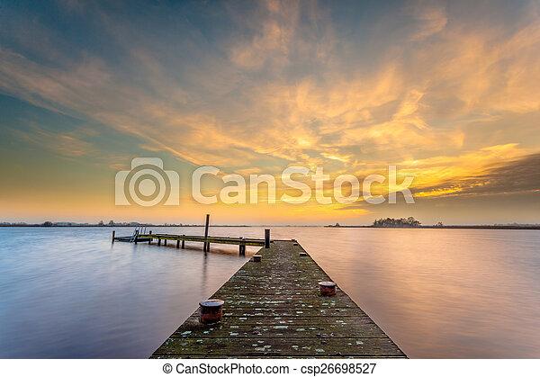 Orange dusk over a tranquil lake - csp26698527