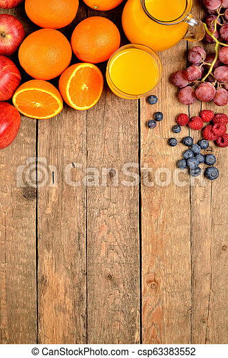Orange juice, fresh oranges, apples, grapes, raspberries and blueberries on a wooden table - fruit background - view from above - vertical photo - csp63383552