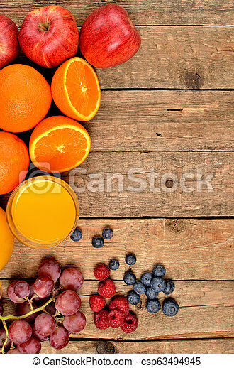 Orange juice, fresh oranges, apples, grapes, raspberries and blueberries on a wooden table - view from above - vertical photo - left orientation frame - csp63494945
