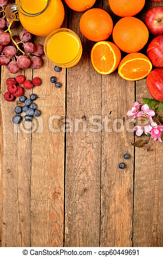 Orange juice, fresh oranges, apples, grapes, raspberries, blueberries and spring flowers on a wooden table - view from above - vertical photo - csp60449691