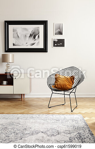 Orange pillow on a black, industrial net chair by a white wall with gallery of mock-up pictures in an elegant living room interior. - csp61599019