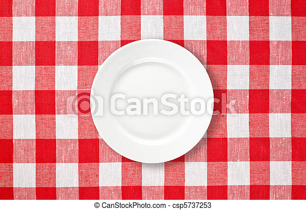 orange plate on red checked tablecloth - csp5737253