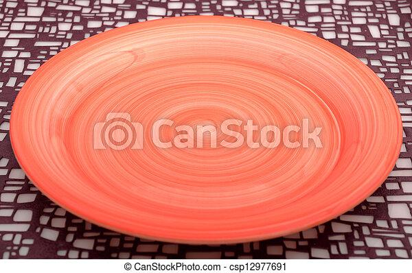 Leere orangefarbene Platte auf dem Hintergrund - csp12977691