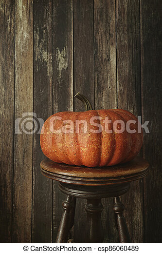Orange pumpkin against wood background - csp86060489