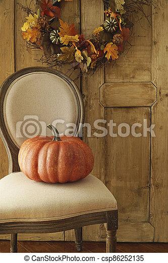 Orange pumpkin on chair - csp86252135
