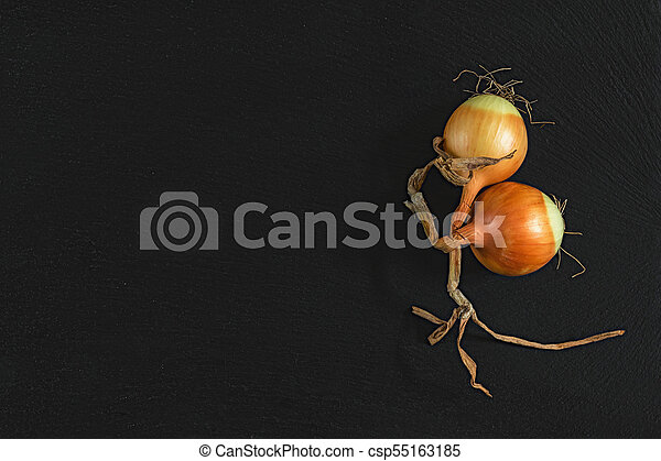 Orange raw two onions on black stone surface. Top view, copy space. - csp55163185