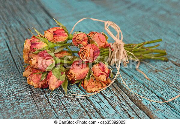 orange rose bouquet on wood - csp35392023