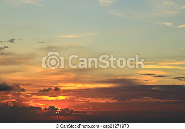 Orange sunset behind clouds and blue sky - csp21271970