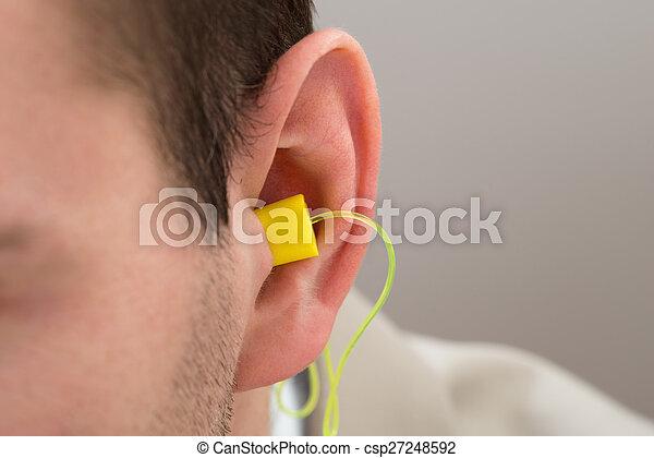 Un tapón amarillo en el oído - csp27248592