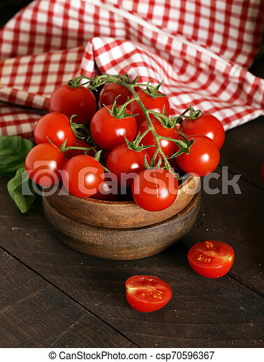 organic vegetables, tomatoes in a wooden bowl - csp70596367