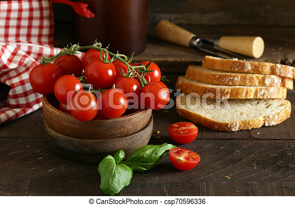 organic vegetables, tomatoes in a wooden bowl - csp70596336