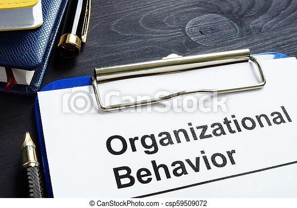 Organizational Behavior report on an office desk. - csp59509072