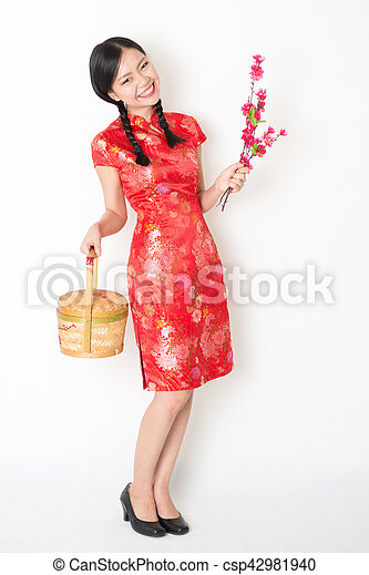 c46f82707 Oriental female in red qipao holding gift basket. Young asian woman ...