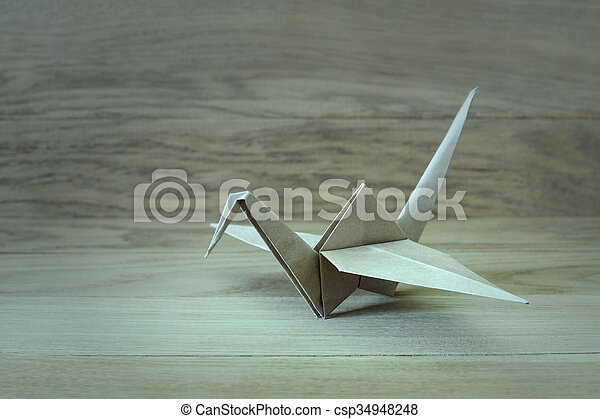 Origami crane on a wooden background - csp34948248