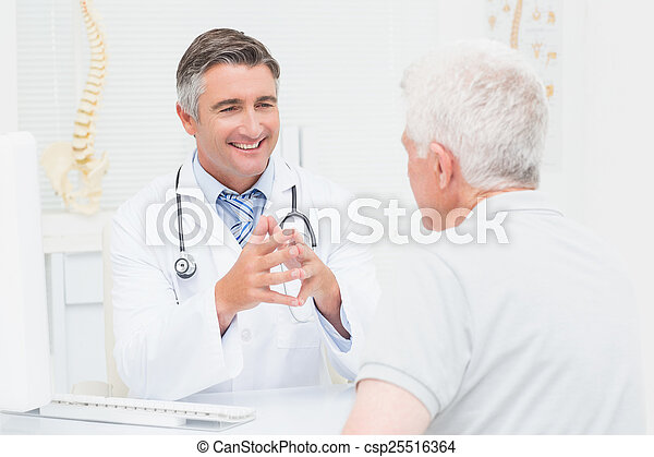 Orthopedic doctor discussing with senior patient - csp25516364